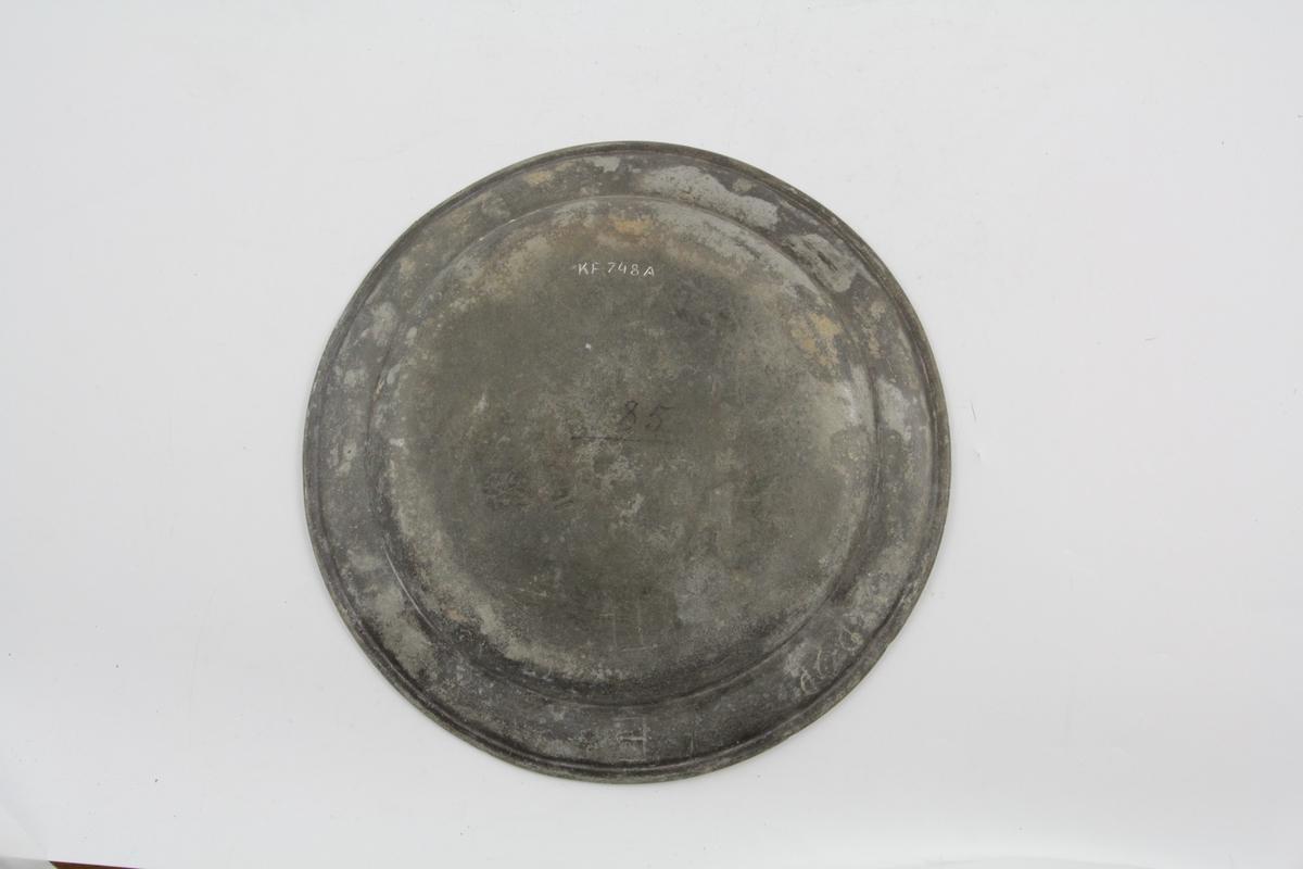 a: tallerken. Flat, sirkelrundt, nesten horisontal kant med gravert linje ved randen.  b: tallerken. Flat (som a).