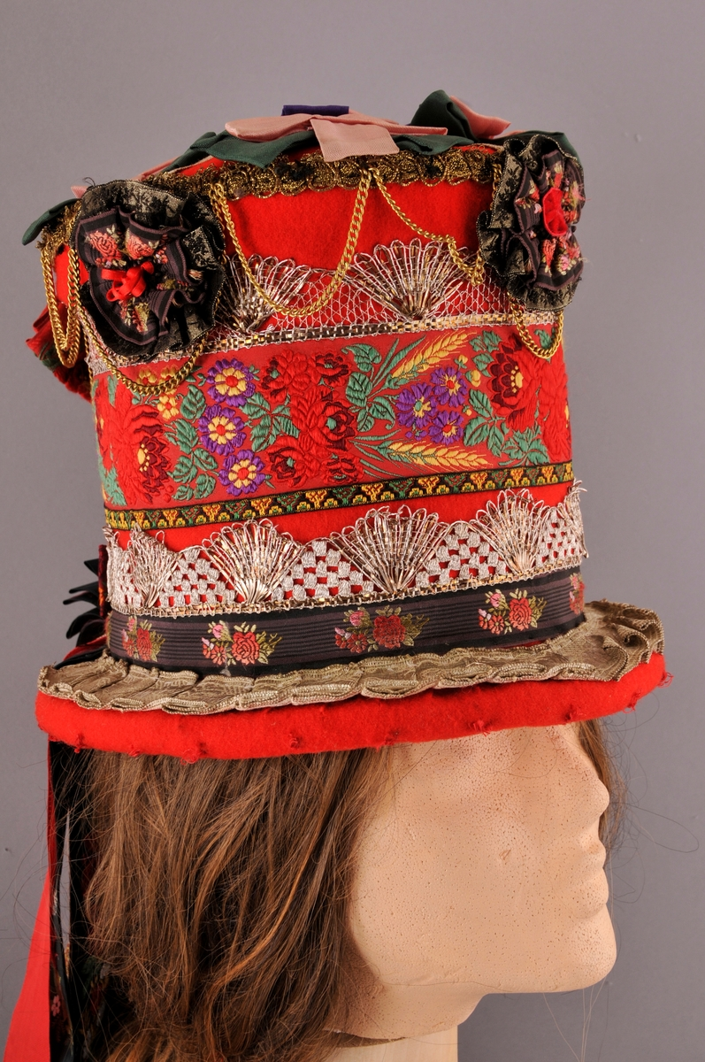 """Brudehatt, nylaga. Oppbygd rundt ein filthatt av Zinkes mote AS. Langs bremmens ytterkant er det lagt ei """"pølse"""" av vatt før heile hatten er kledd med høgraudt klede med tydleg lerretsvev. Inni går den raude kleden litt over halvvegs opp i hatten. Der er det  sydd ein løpegang med eit band til å dra saman vidda med, dette for at hatten skal slutte betre rundt hovudet.  På bremmens overside er ei sylvbore foldelagt og sydd fast langs innerkanten, denne bora er truleg ikkje ny. Vidare rundt hattens pull er det sydd fast eit band med lansert blomemønster, ein sylvknipling, eit smalt band med brodsjert mønster og ein sylvblonde (ulik den som er lenger ned) og til slutt ei avklypt gullblonde/agraman heilt på toppen av pullens kant. Banda er i ein blandingskvalitet. Over pullens topp (flat del) er ei sylvbore lagt i kryss, over denne er det festa rosettar sydd av grønt, lilla og rosa syntetisk band. Langs kanten av pullen er det sydd fast 3 rosettar, ein midt framme og ein på kvar side. I tillegg er eit """"gull""""-kjede av uedelt metall sydd fast så det heng i ujamne bogar. Midt bak på hatten er det øverst sydd fast ei sløyfe av eit lansert bomullsband og ei mindre sløyfe nederst av eit mønstervove band. i tillegg ni lange heng av band, både einsfarga og mønstervove."""