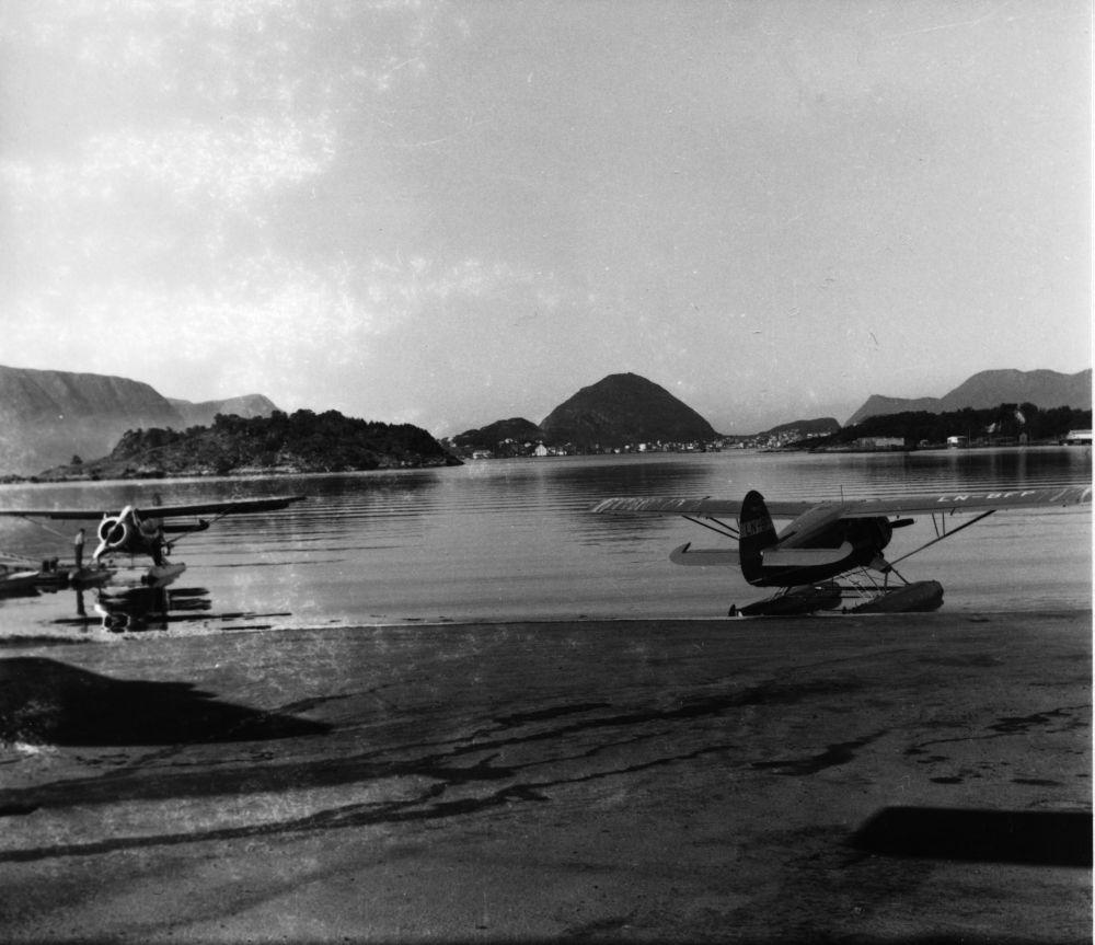 Landskap. To fly av typen Norseman fra Widerøe, fortøyd i strandkanten. Det en ligger ved flytebrygge. En person ved flyet. Det andre flyet, LN-BFP, fortøyd i fjæra. I bakgrunnen skogkledde åser og en tettbebyggelse.