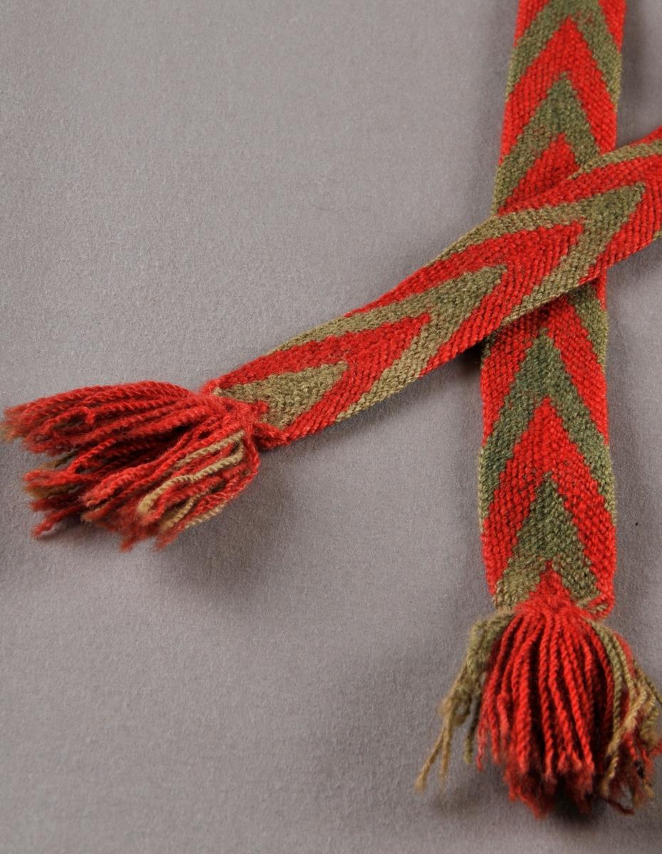 Sokkeband laga av totråds grønt og raudt ullgarn. 20 trådar raudt og 20 trådar grønt. Det eine bandet er stoppa med mørkare grønt ullgarn i kanten.