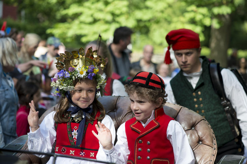 Jente i bunad med krone og blomsterkrans på hodet og gutt i bunad sitter vogn trukket av hest.