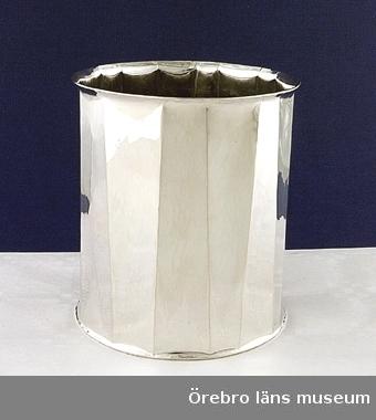 Vas av silver. Stämplar BUL inringat rektangulärt, ST. ERIK, KATTFOT, S, 925 inringat rektangulärt följt av B10 inrigat rektangulärt. Tillverkad i Stockholm.Tillverkare BENGT LILJEDAHL E HUtställt i Länsmuseet, Klenodkammaren 18/6 2000.Mått: H  110,50 mm  Diam  100 mm  Vikt  412 gr.Greta Hamilton köpte vasen av Bengt L 1977.Vasen ingår i en gåva som museet fick genom testamente av Märta Hamilton,s dödsbogenom Anne M-L von Schoting.Styrelsen beslöt att museet med tacksamhet skall mottaga donationen.Bilaga finns i bilagepärmen.