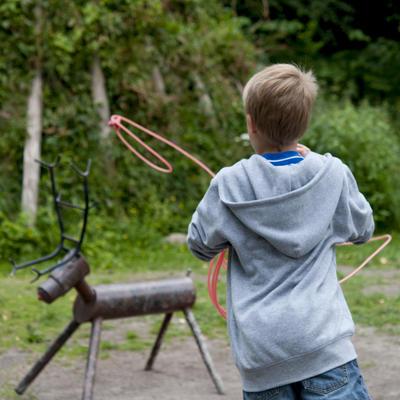 Gutt øver seg på lassokasting på et lite reinsdyr av av jern