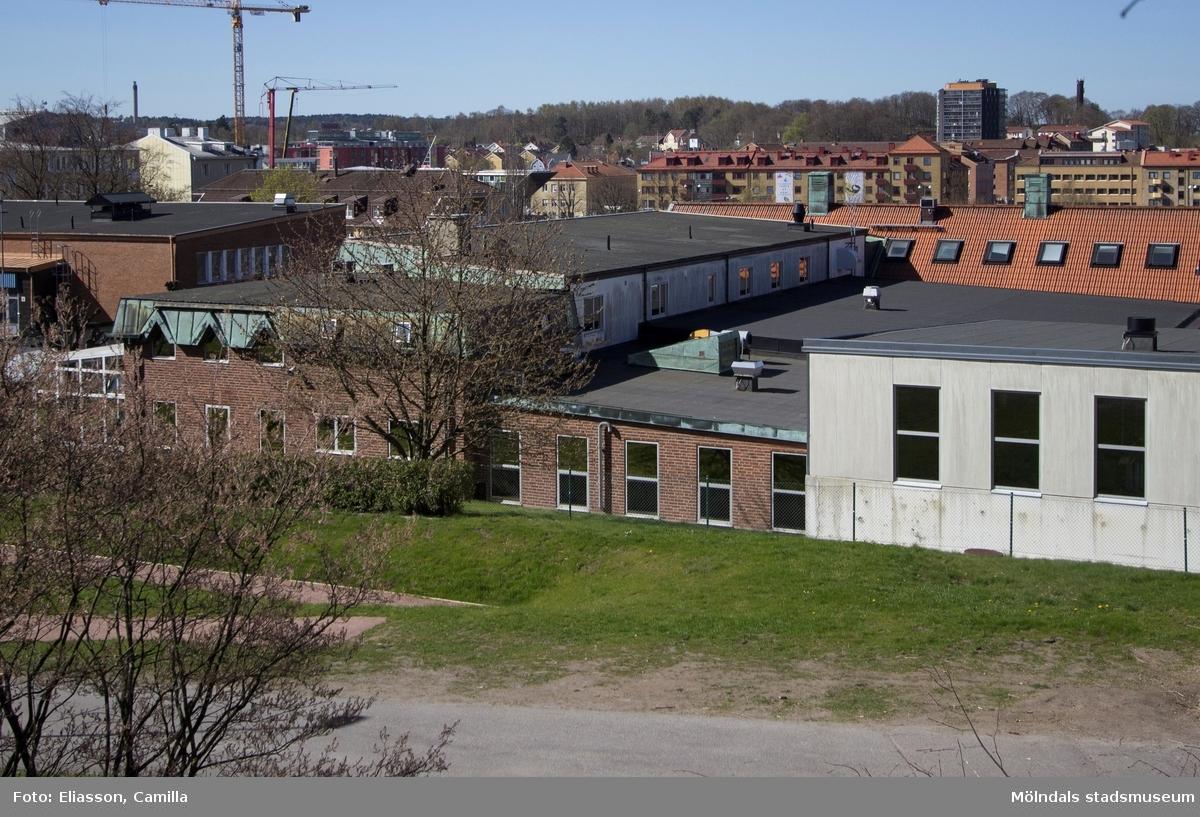 Den bild är tagen strax bakom nuvarande Mölndals brandstation. Här ser man brandkårens område och all den bebyggelse som vuxit upp i närheten. En lyftkran står mitt i nybygget av SCAs stora vita kontorsbyggnad. Till höger, på andra sidan motorvägen, ligger Mölndals centrum samt det mörkgråa höghuset som ligger på Storgatan 32A.