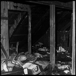 Ødeleggelser etter brann på loft i firemannsbolig.