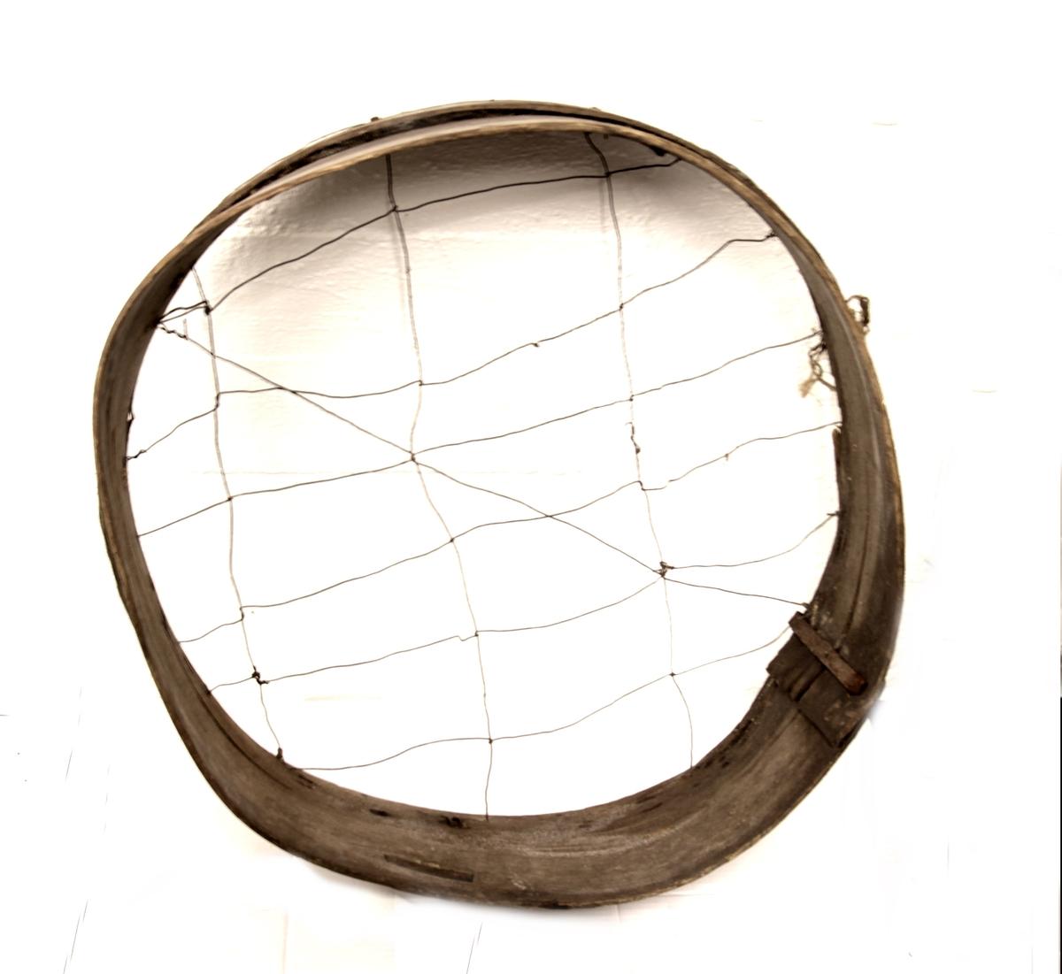 Båndene er festet med et metallbeslag og bunnen består av store og åpne masker.