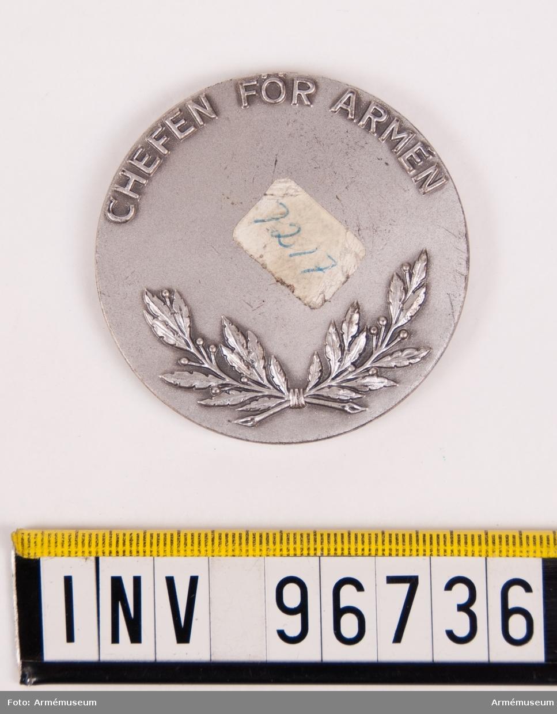 Medalj i silver för Chefen för armén. Åtsida till medalj upptagande sköld med 3-kronor, skölden krönt av kungl. krona, det hela liggande på korslagda svärd. Frånsida till medalj upptagande lagerkvistar och inskription CHEFEN FÖR ARMÉN jämte plats för ingravering av namn, årtal etc.  Stans nr 27575, 27576. Stans härdad 1962-01-25.