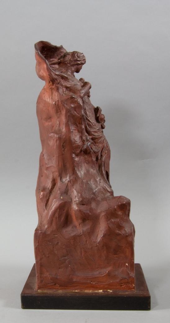Kvinna, Sappho, stående håller en trälyra med metallsträngar i ena handen. I andra handen, tryckt mot bröstet, blommor. Lutad mot klippformation.
