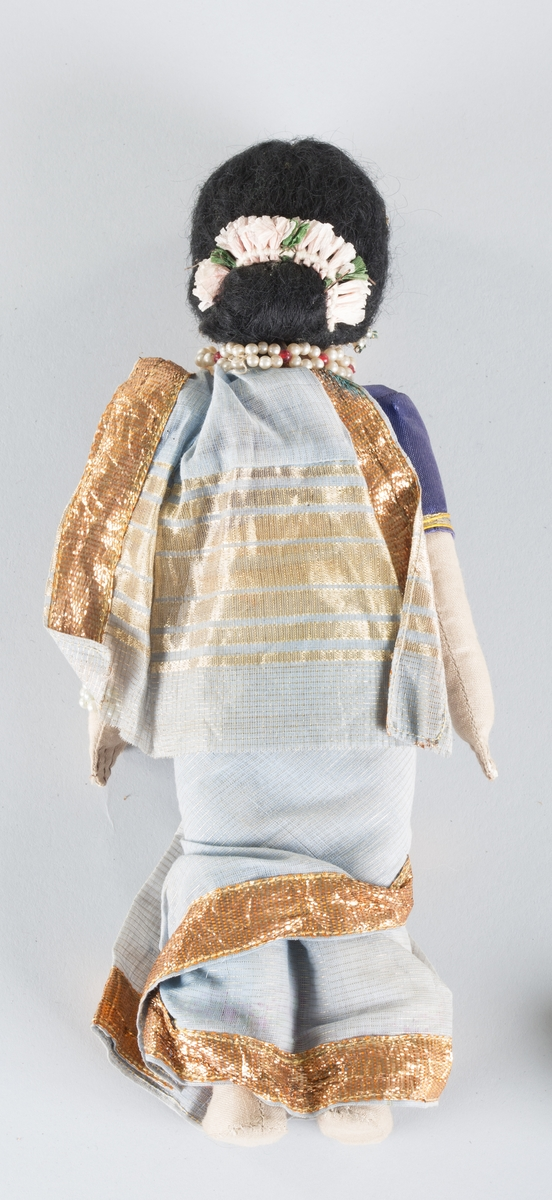 Dukke ikledd bekledning i lyse blåtoner, med broderier og smykker.