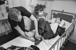 Äldre man får hjälp med sina skor, Tunåsens sjukhem, Uppsala