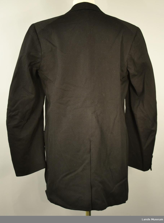 I svart klede, silkeslag og bomullsfor; lyst med svart og lilla striper i erme. Lukket med ein knapp, to små knapper på kvart erme. To lommer + en innerlomme. Slitt bak. Skreddersydd.