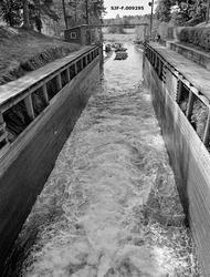 Fra slusekammeret i Strømsfoss sluse i Aremark i Østfold.  Fotografiet er tatt høsten 1982, som var den siste sesongen med tømmerfløting i Haldenvassdraget.  Vi ser fra øvre sluseport mot slusekammeret, som var sprengt ned i berget.  Langs de loddrette sideveggene hadde man plassert pælerekker som bar arbeidsplattformene på begge sider.  På de samme pælerekkene var det dessuten spikret glatte bordevegger, som skulle hindre at slusingsgodset hektet seg fast i ujevne bergflater eller pæler.  Da dette fotografiet ble tatt fosset det kvitskummende vann fra lukene i ovenforliggende sluseport gjennom slusekammeret.  Dette ble gjort for å «spyle» forrige slusevending, fire sammenlenkede tømmerbunter, ned i underkanalen.  Der ble flere slike slusevendinger bundet sammen i lengre lenker, som etter hvert skulle samles i større slep og bukseres videre nedover i vassdraget.  En liten historikk om tømmerfløting og kanaliseringsarbeid i Haldenvassdraget finnes under fanen «Opplysninger».