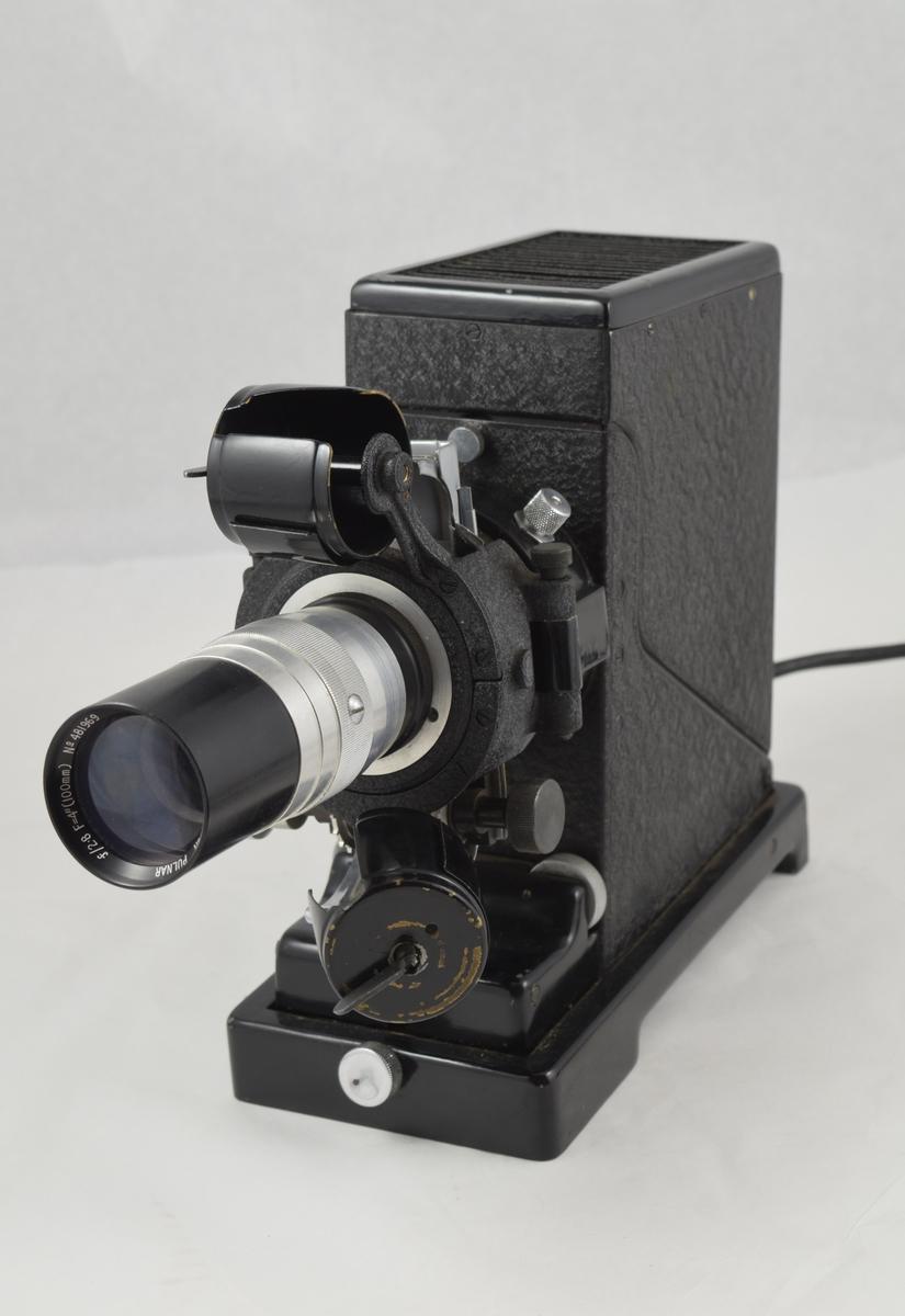 Lysbildefremviser i trekoffert med tilhørende utstyr. Fremviser til film på rull. Stående rektangulær form med lang linse fra kortsiden.