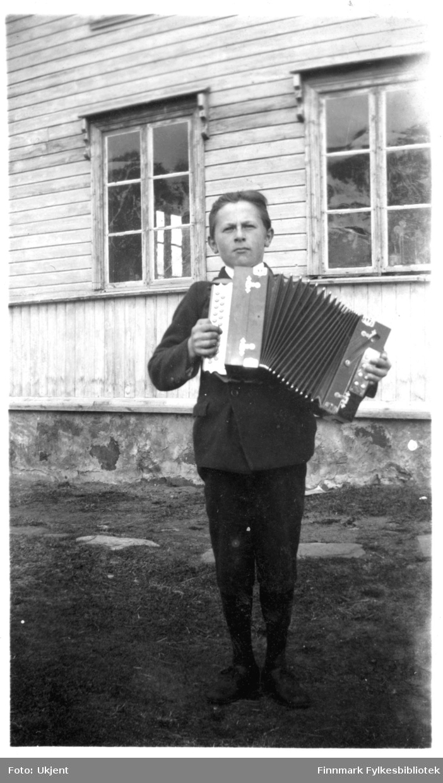 Anton Mathisen avbildet her med et trekkspill i hendene. Han er kledd i jakke, knebukser, sokker og sko. I bakgrunnen kan man se et trehus med grunnmur og vinduer.