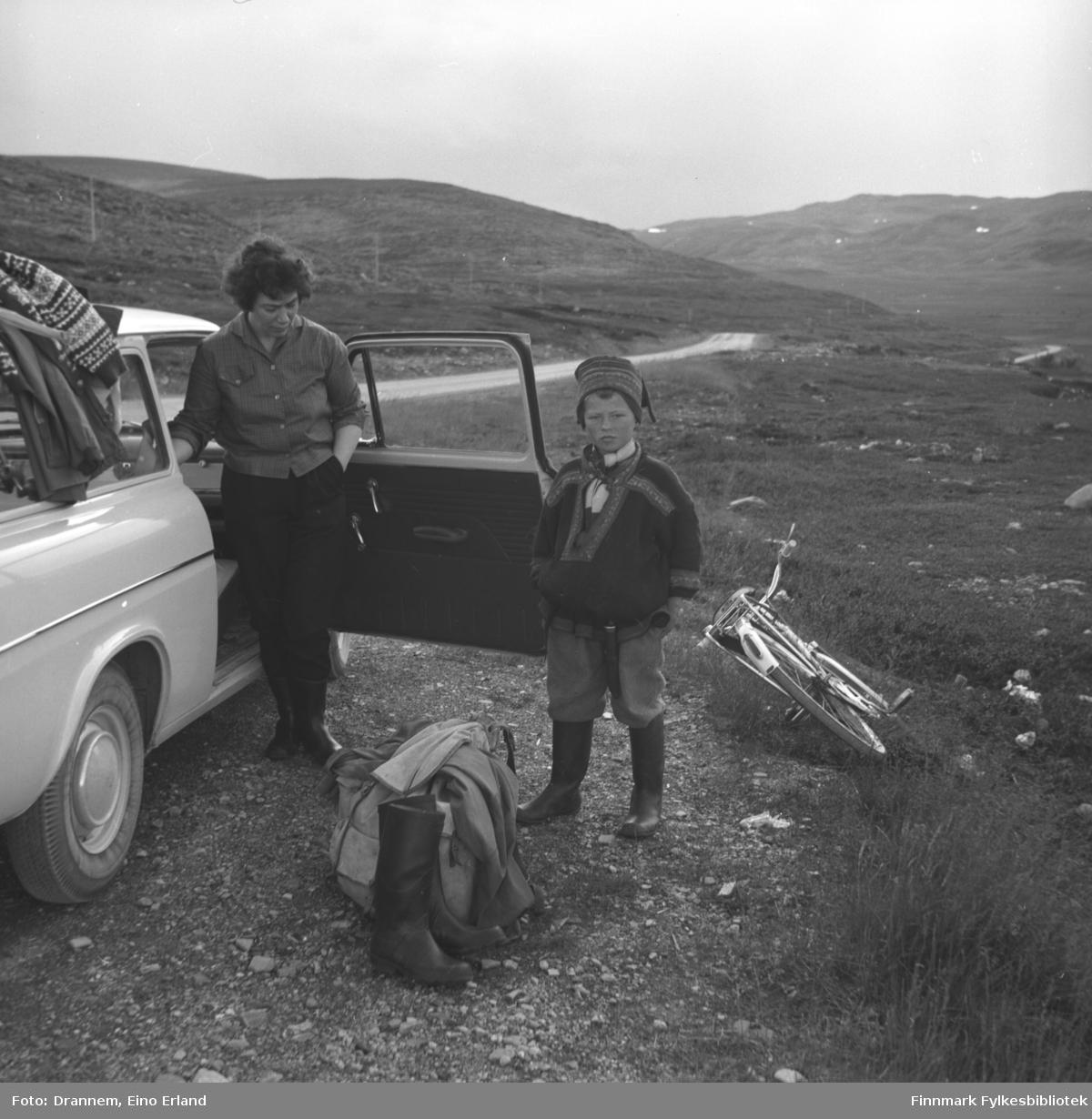 Jenny Drannem står ved siden av familiens bil på Rv98, Ifjordfjellet. En ukjent gutt iført sameklær står ved siden av.