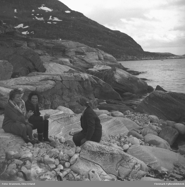 Tre damer sitter i fjæra utenfor Hammerfest. Jenny Drannem i midten, de to andre er ukjente. Stedet kan være Skjærvika, litt nordvest for Hammerfest.