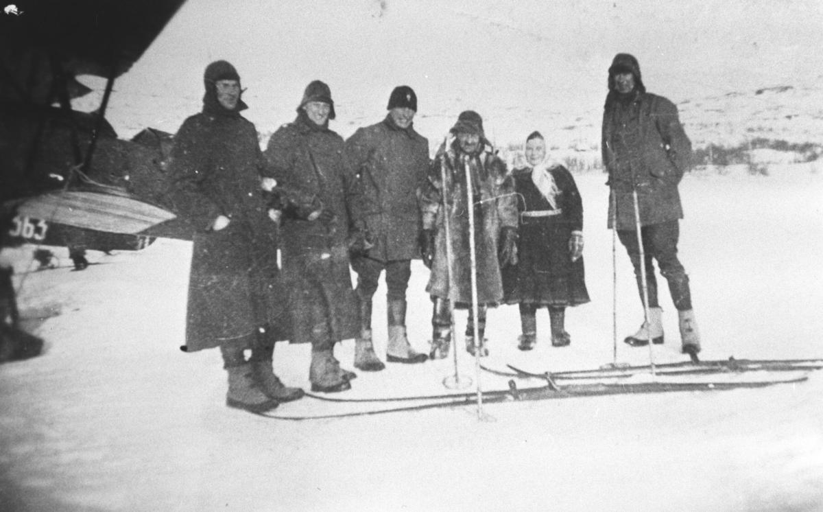 """""""Fly på Andrevann"""". Bilde fra Andrevann, 1934. Det er vinter og is på vannet. I bakgrunnen ser vi deler av et fly. Fem menn og en kvinne står midt på bildet med to par ski foran seg. Fire av mennene har på seg frakker og skiller seg tydelig ut ifra de to andre, som er kledt i pesk og kofte. De fire er nok flygere."""