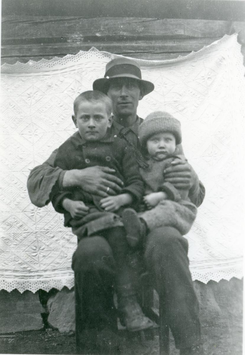 Portrett av Anders Haugen som holder sønnene Norvar og Ola.