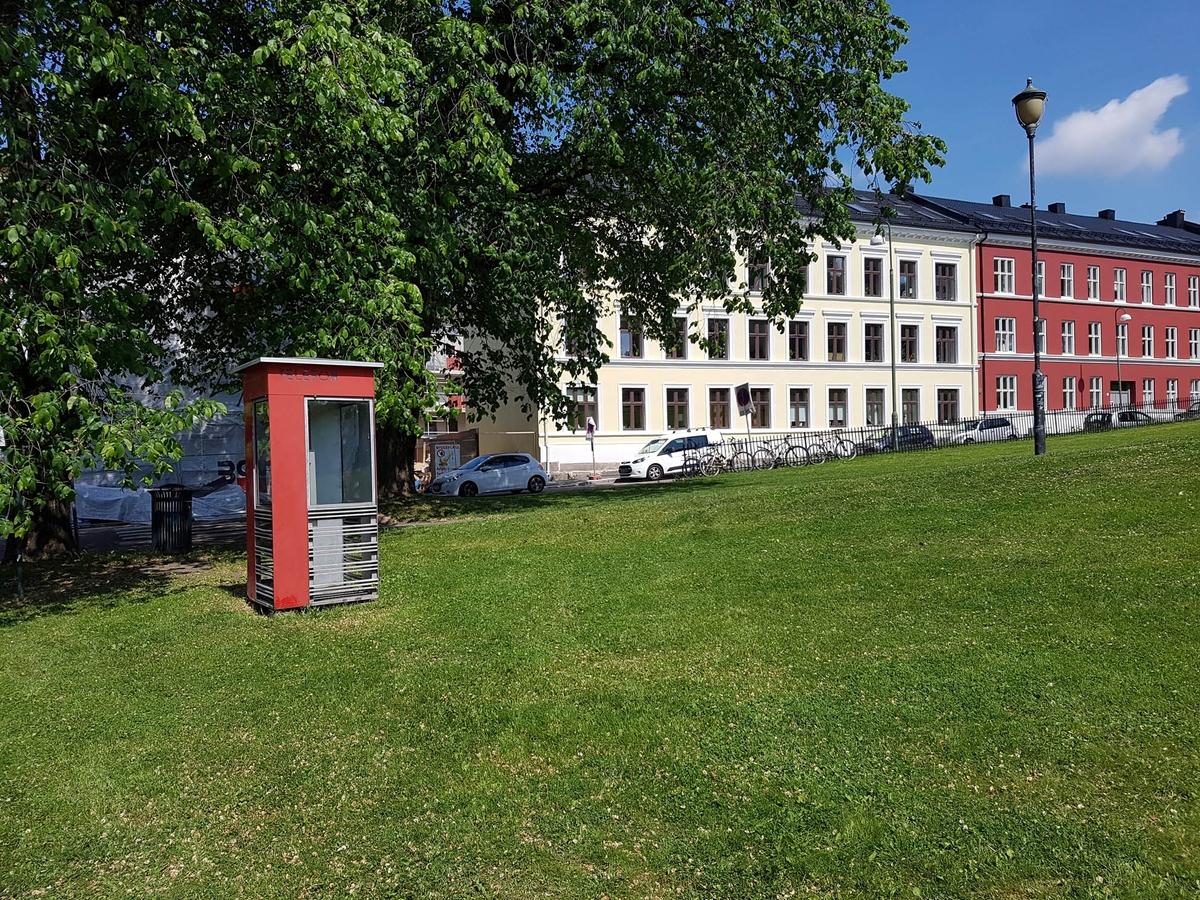 Denne telefonkiosken står i Danmarksgata/Opplandsgata ved Vålerenga kirke. De røde telefonkioskene ble laget av hovedverkstedet til Telenor (Telegrafverket, Televerket) Målene er så å si uforandret.  Vi har dessverre ikke hatt kapasitet til å gjøre grundige mål av hver enkelt kiosk som er vernet.  Blant annet er vekten og høyden på døra endret fra tegningene til hovedverkstedet fra 1933. Målene fra 1933 var: Høyde 2500 mm + sokkel på ca 70 mm Grunnflate 1000x1000 mm. Vekt 850 kg. Mange av oss har minner knyttet til den lille røde bygningen. Historien om telefonkiosken er på mange måter historien om oss.  Derfor ble 100 av de røde telefonkioskene rundt om i landet vernet i 1997. Dette er en av dem.