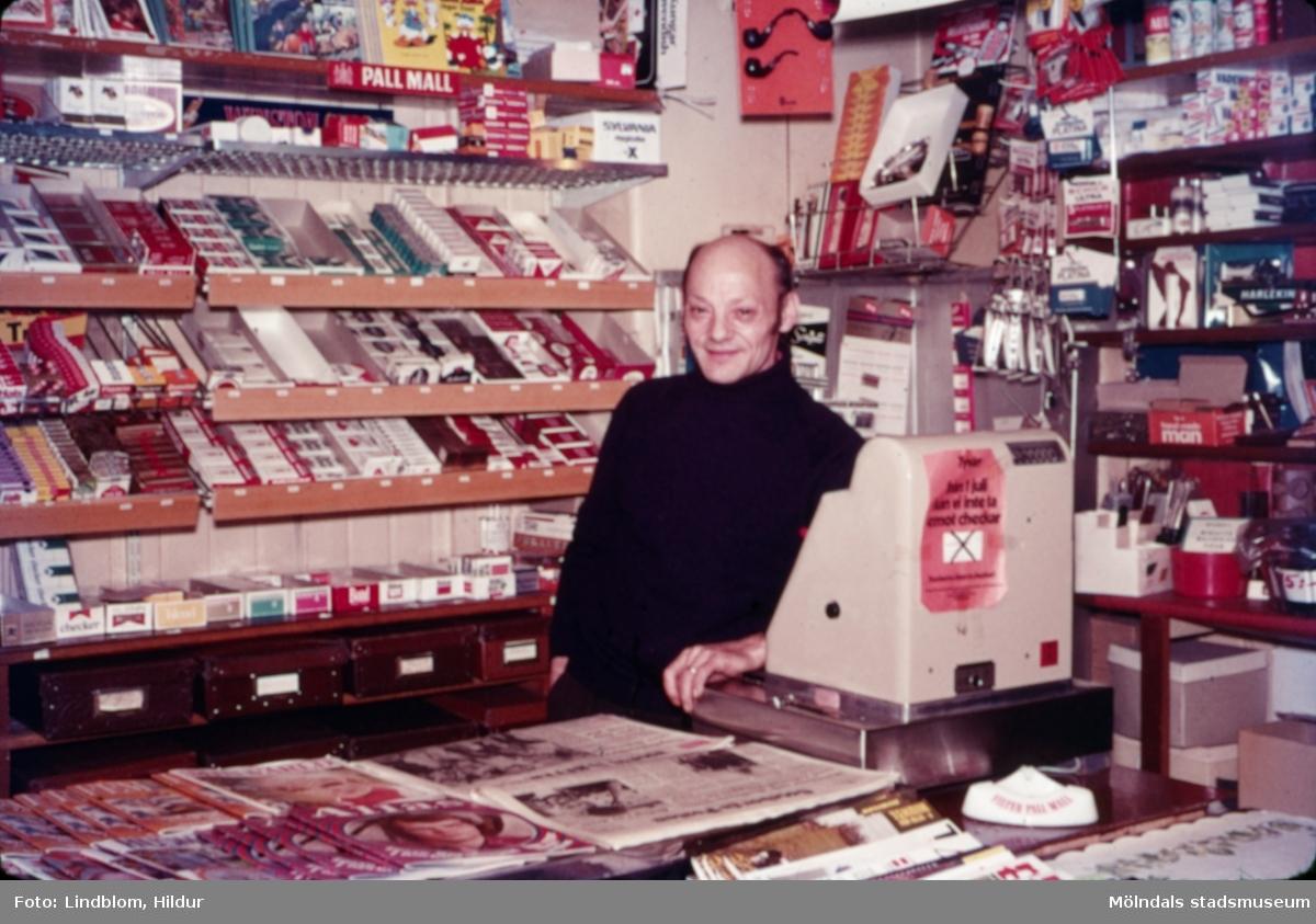 En man står vid kassan i tobaksaffären vid Gamla Torget i Mölndal med adress Kvarnbygatan 45, 1970-tal. Mannen hette eventuellt Lagher i efternamn. Huset används numera av Kvarnby bageri.  För mer information om bilden se under tilläggsinformation.