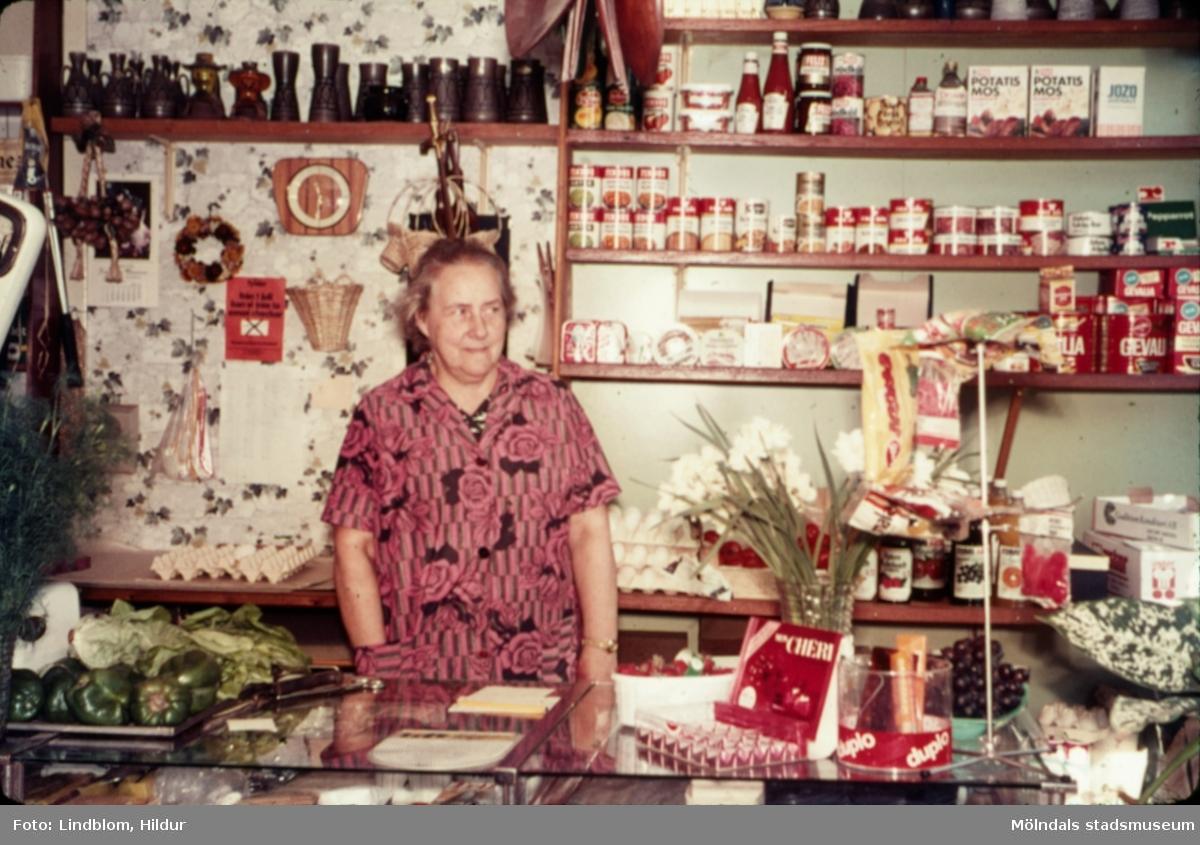 En kvinna står bakom disken i en speceriaffär, troligtvis vid eller i närheten av Gamla Torget i Mölndal, 1970-tal.  För mer information om bilden se under tilläggsinformation.