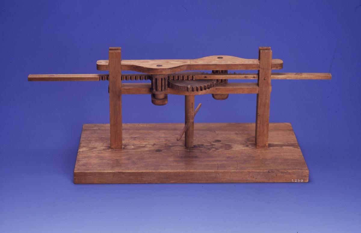 Kopia av modell, Polhems mekaniska alfabet. Vid rotation av den lodräta axeln erhålles en fram- och återgående rörelse hos kuggstången. Text på föremålet: LXXXV.