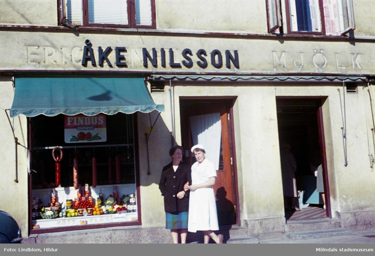 Två kvinnor står utanför dörren till Åke Nilsson charkuteri och delikatesser med adress Kvarnbygatan 43 vid Gamla Torget i Mölndal, 1960-1970-tal.  För mer information om bilden se under tilläggsinformation.