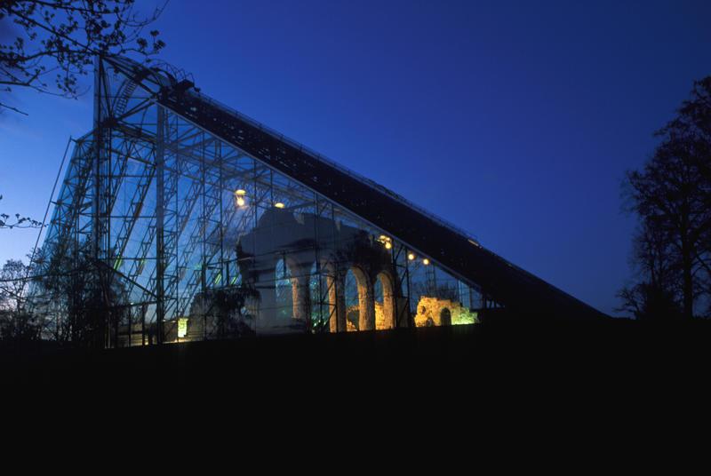 Domkirkeruinen under vernebygget i glass og stål er delvis opplyst og delvis i silhuett mot en mørkeblå kveldshimmel.