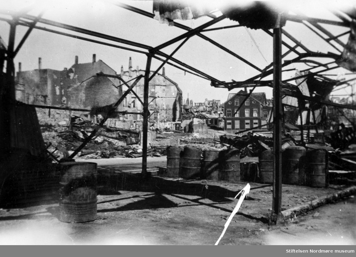 """Krigen har kommet til Kirkelandet i Kristiansund. Etter nazistenes herjinger i perioden 28. april til 1. mai 1940 ligger nå store deler av byen i ruiner.  Etter bombigen løp det totale antall brente bygg på tilsammen 767, hvor 605 av disse var på Kirkelandet og 162 på andre """";land""""; i Kristiansund. Her fantes det til blant annet til sammen 3906 boliger ifølge boligtellingen av 1938, og av disse brant 2162 boliger ned og 7099 mennesker ble husløse. I tillegg til de 767 brente byggene brant 36 fiskepakkehus ned til grunnen, hvorav 34 lå på andre """";land"""";. Verdien av de brente byggene beløp seg til kroner 26,9 millioner for Kirkelandet (kroneverdi per 1940) eller tilsammen 30,6 millioner kroner (kroneverdi per 1940) for hele byen. Fra Nordmøre Museums fotosamlinger. Kilde: Gjenreisningsproblemer i Kristiansund. Fremlagt ved gjenreisningsinstituttet i Kristiansund. Juli 1945. Side 16 - 20."""