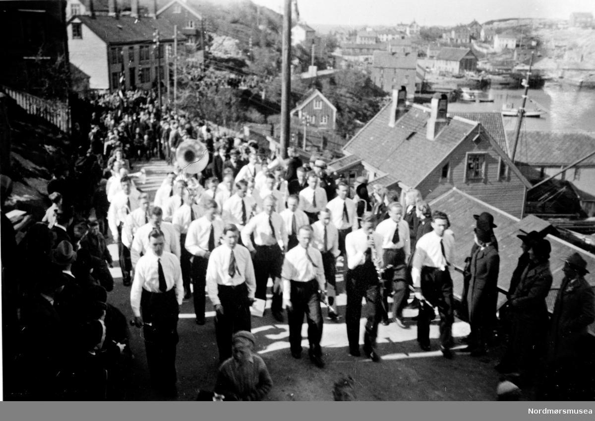 """Dette er Tempo, enten fra Fredsmarsjen den 8.mai eller fra Fredskonserten i Vanndamman den 12. mai. Ifølge referat stilte korpset i hvite skjorter og mørke bukser.  17 mai var ikke været  like bra, så da stilte korpset i """"vanlig"""" dress. Dessuten gikk ikke Tempotoget i Vågen. Ifølge John Solbakk (sekretær i Tempo i 1945) var ruten til Tempotoget som følger:""""Vi marsjerte ned Langveien til Grand Hotell hvor vi spilte et par nummer fra balkongen (hvordan fikk de plass??) . Herfra gikk ruten til Sykehuset, videre over Sykehusenga til Marstrandsgate, opp denne, ned Fløiveien, hvor Johan Myklebust fikk høre «Ja, vi elsker». Opp Clausens gt, Vardeveien, Kåsbøls vei, gjennom brakkestrøket, ned Langveien til skolen. Derfra fulgte kransepålegging på Moses- støtten, minnebøssene og Christiestøtten. """" (info fra Øyvin Dall-Larsen 2017),  Toget passerer Mellemværftet i Kranaveien. Musikkorpset Tempo hadde lokaler i Roklubben, seinere Edvard Fladseths blikkenslagerforrertning, nå 2017 Levende Vågen. Fra Nordmøre Museum sin fotosamling"""