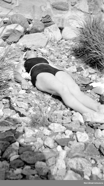 Portrett av en kvinne liggende i solen ute en sommerdag. Det er usikkert hvem vi ser på bildet, samt når og hvor bildet er tatt. Fra Nordmøre Museums fotosamlinger.