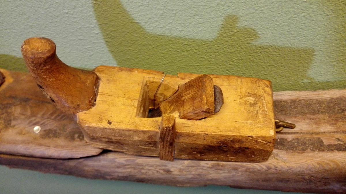 """1 strekeslev (profilhövl).  En """"strekeslev"""" (Leikanger) eller profilhövl. Stokken av bjerketræ og av fasong som en kosthövl med haandtag foran. Paa begge langsider """"strekfisk""""-fure for ansatsfurer(?)  Kjöpt av Ola Henjesand, Eidet, Kaupanger."""