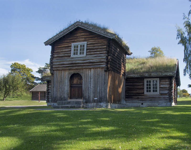 """Lav, grå tømmerbygning med gress på taket og toetasjers tilbygg, et såkalt """"barfrø"""" midt på langveggen. (Foto/Photo)"""
