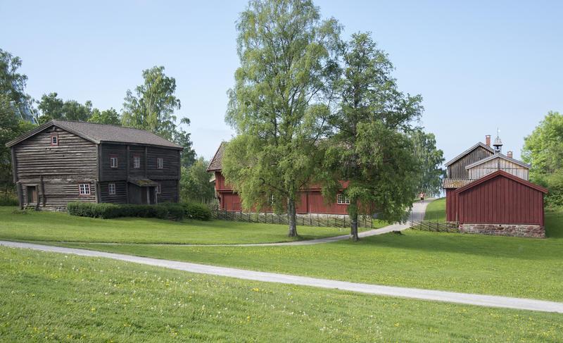 Hedmarkstunet består av en grå tømmerbygningn i to etasjer til venstre i bildet, midt på ser vi to bjørker og til høyre en rød, plankebeslått bygning. (Foto/Photo)