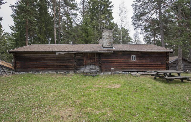 Langt størhus i brunlig tømmer, med stor plen og et parkbord utenfor.