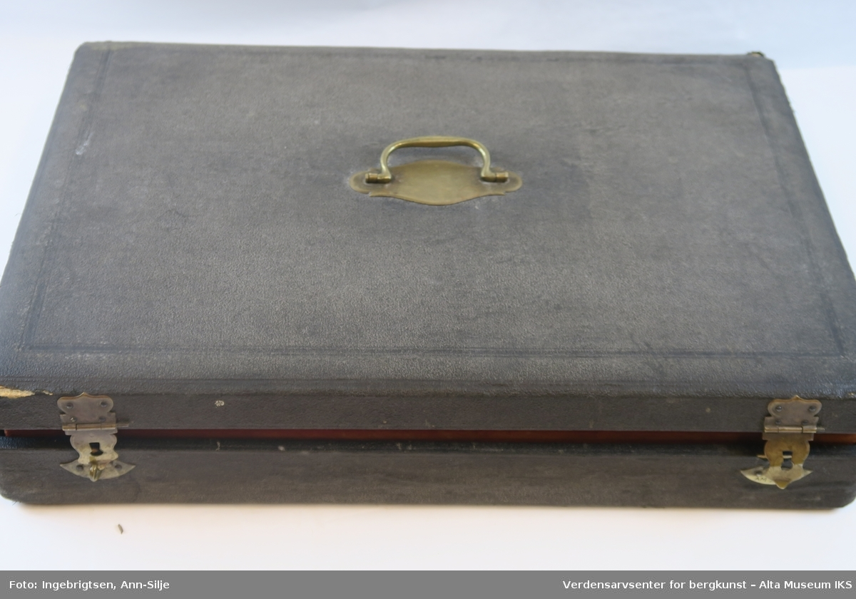 Rektangulær koffert med 12 mindre kniver (til frokost) og 24 større kniver (til middag). Knivene ligger pent anrettet i rødtrukket bestikkasse. Knivene har hvite håndtak og metalfarget knivblad.