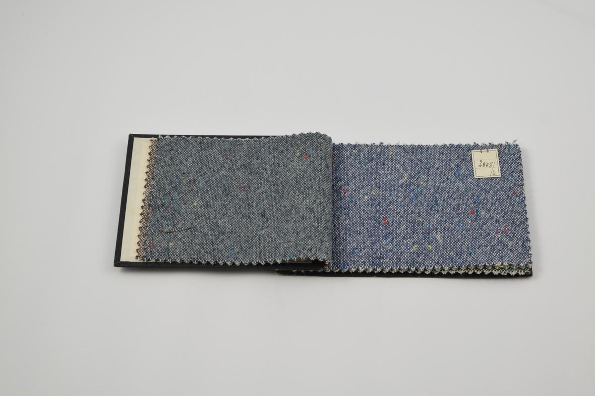 Prøvebok med 7 prøver. Middels tykke ullstoff med tilfeldigplasserte prikker i ulike farger. Alle stoffer er merket med en firkantet papirlapp festet med metallstifter hvor nummer er påskrevet for hånd.   Stoff nr. 2008/4 (brun), 2008/5 (blå), 2008/6 (blå), 2008/7 (lys grå), 2008/8 (grønn), 2008/9 (mørkere brun), 2008/10 (enda mørkere brun).