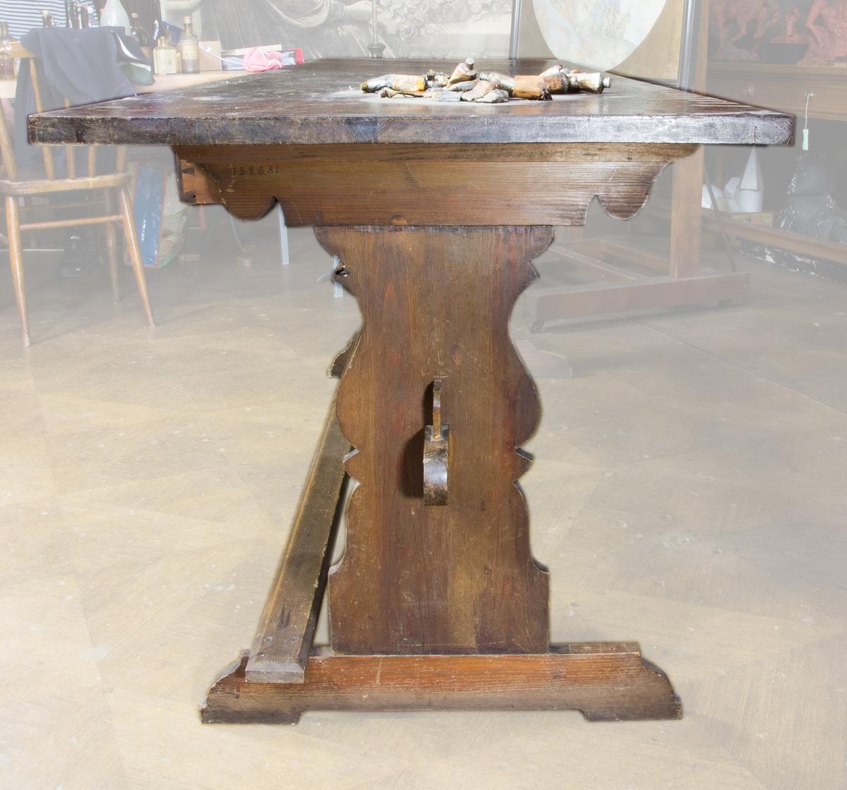 Bord, bockbord av brunbetsad furu. Rektangulär skiva, profilerade gavelben. Tre lådor med dragknoppar. Fotstöd längs ena sidan. Oljefärgsrester och fläckar på skivan.