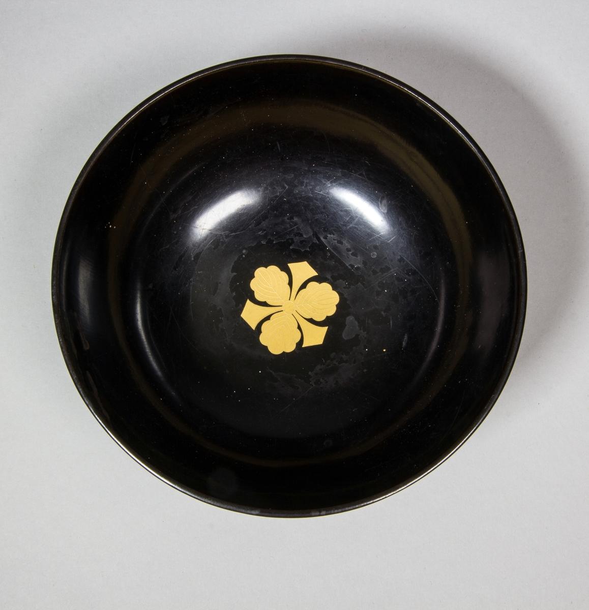Skål, halvsfärisk, av svart lack. Invändigt inlagd guldfärgat blomliknande ornament.