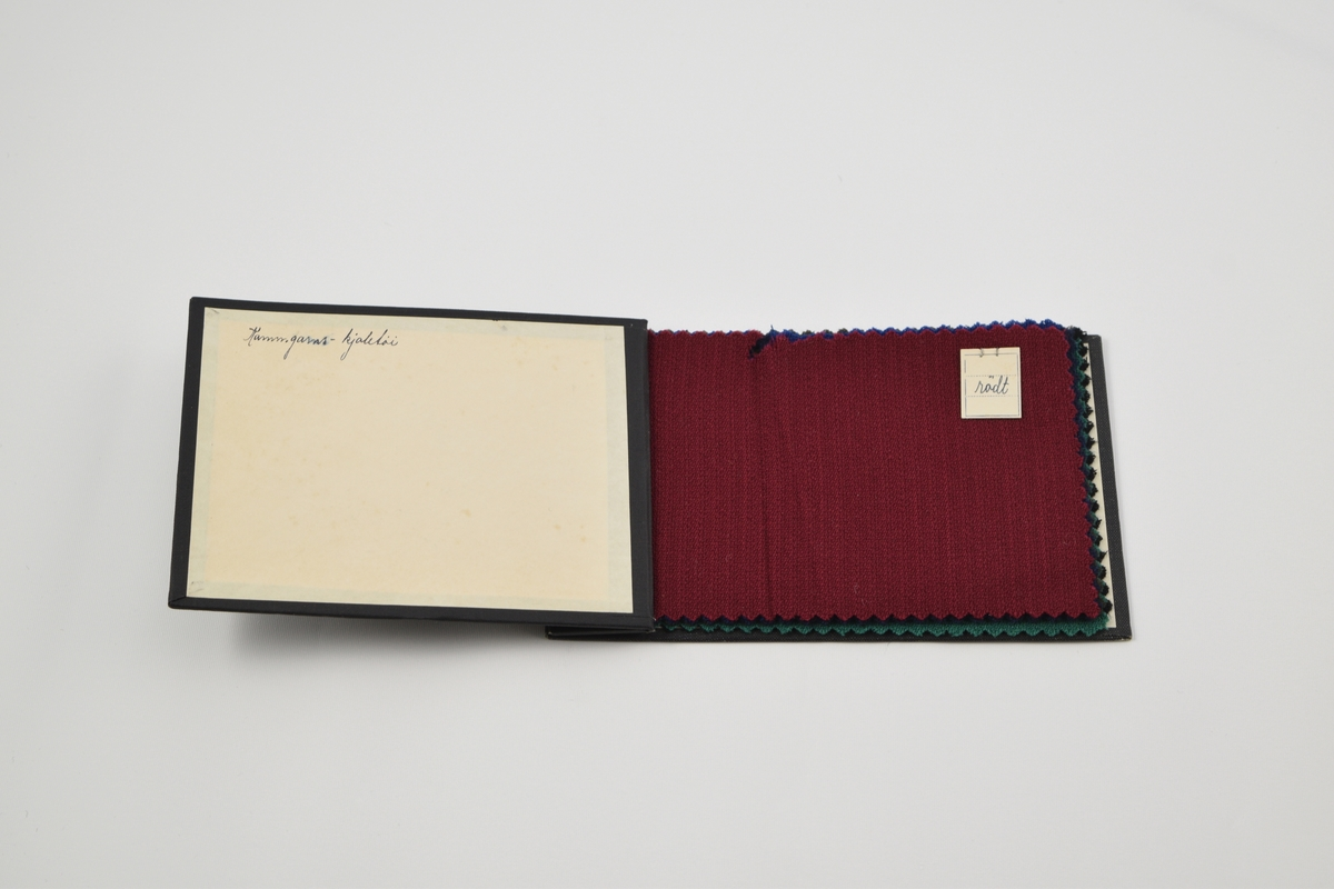 Prøvebok med 6 prøver. Tynne ensfargede ullstoff med diskret striper i vevmønsteret. Alle stoff er merket med en firkantet papirlapp festet med metallstifter hvor fargen er påskrevet for hånd.   Stoff beskrivelse: Kammgarns-kjoletói/rödt, mellom-blått, marineblått, brunt, grønt, sort.