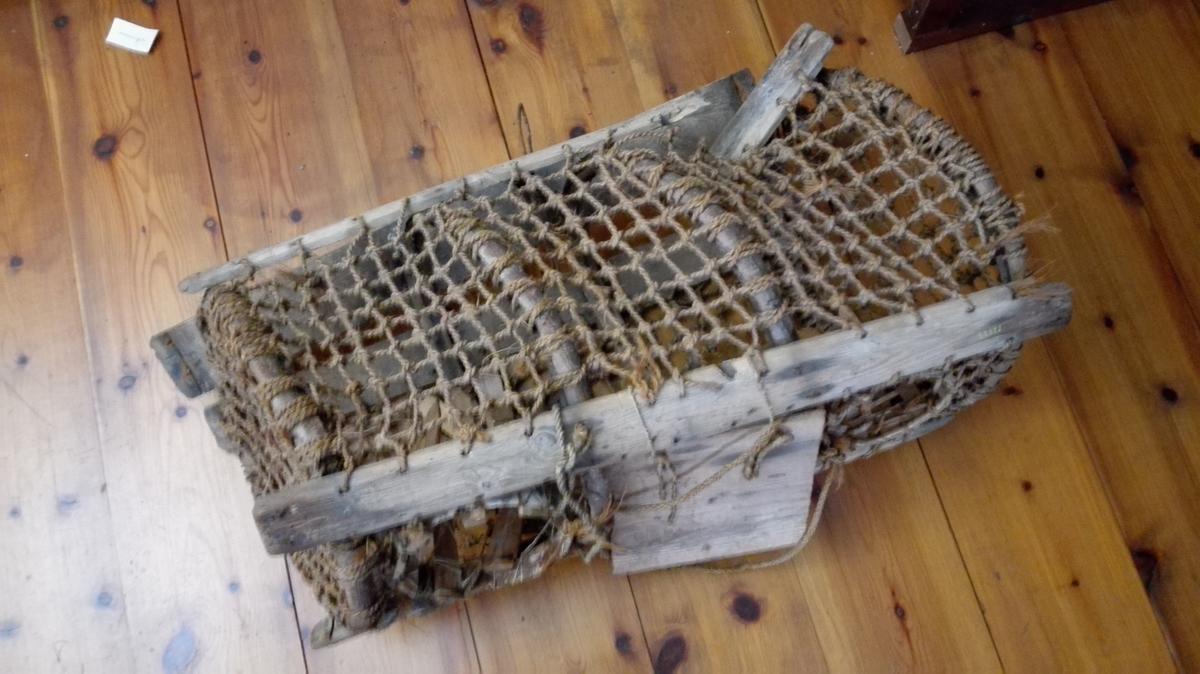 """1 hummerteine  Hummerteine av gammel type fra Gulen. Sylinderformet. Laget av fire solide töndebaand. I bunden paaslaaet utvendig fire töndestaver. Gavler og sider dækket med grovmasket not bundet av tykt snöre. Øverst paa siderne paaslaaet 2 gamle töndestaver. Mellem disse i midten en firkantet luke, hvorigjennem hummeren tas op, paa begge sider av luken 2 runde spiletrakter, hvorigjennem hummeren gaar i teinen. I bunden av teinen ligger en stein, forat faa teinen tilat synke. Teinens længde ca 72 cm og diameter 33 - 40 cm.  Samtlige forannevnte gjenstander (12815 - 12842) fandtes i den gamle """"Bondestue"""" paa Glavær, hvilken er indkjöpt med inventar til samlingerne. Josefine Mehus paastod imidlertid, at hun eiet endel av gjenstandene, bl.a. 12815, 12816, 12817, 12819, 12820, 12827, 12828, 12829, 12832 og 12842. Da eiendomsretten var uviss, avfandt jeg mig med hende mot et vederlag av kr. 25.  Kjöpt av Josefine Mehus, Glavær."""