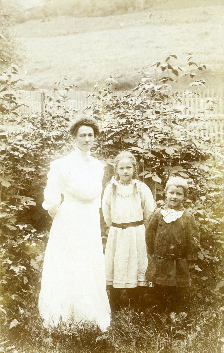 Prospektkort av to barn og ei kvinne som står ute i ein hage.
