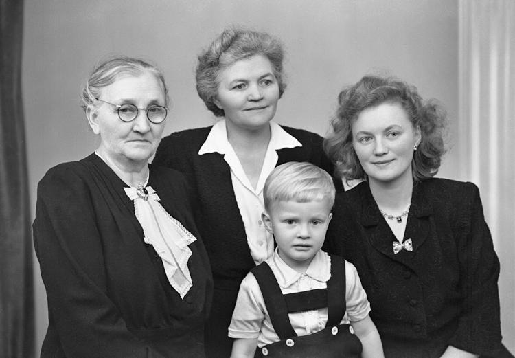 Foto av fyra generationer. Tre kvinnor i olika åldrar och en pojke i hängslebyxa. Ateljéfoto.