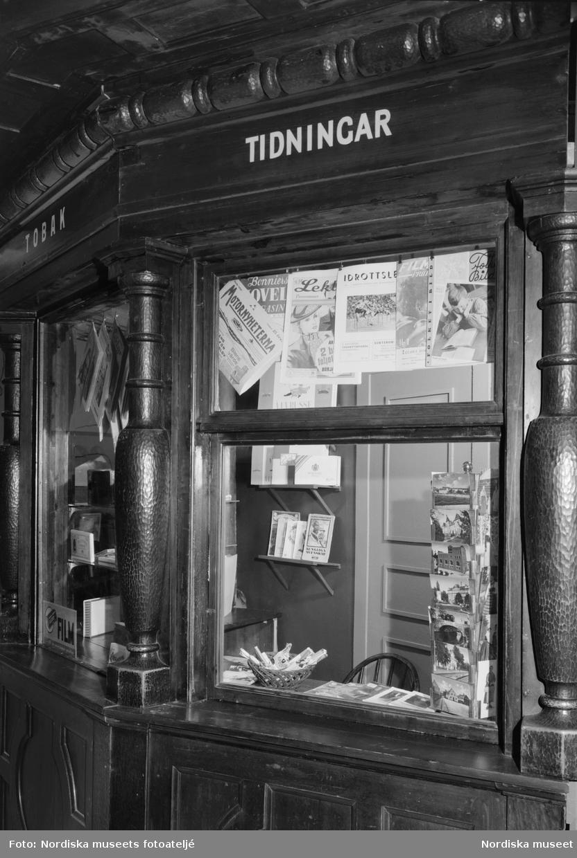 """Pressbyråkiosk/tidningskiosk uppbyggd i avdelningen """"Krig och kriser"""" i block 13 på Nordiska museets jubileumsutställning """"Svenskens 100 år - känn dig själv"""". Exteriören är byggd av mörkt trä med paneler och skuren dekor. På var sida om kioskluckan står en profilerad kolonn. I fönstren hänger tidningar och tidskrifter."""