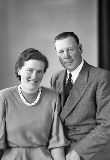 Foto av ett medelålders äkta par. Hon är klädd i färgad klänning med halsband. Han är klädd i kostym med slips.Midjebild. Ateljéfoto.