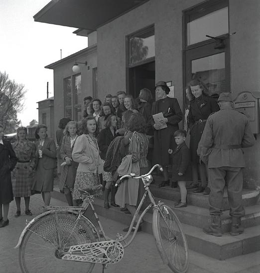 Betplockarna, 1942. Ett antal tonårsflickor har samlats på trappan utanförjärnvägsstationen i Växjö, innan avfärd.