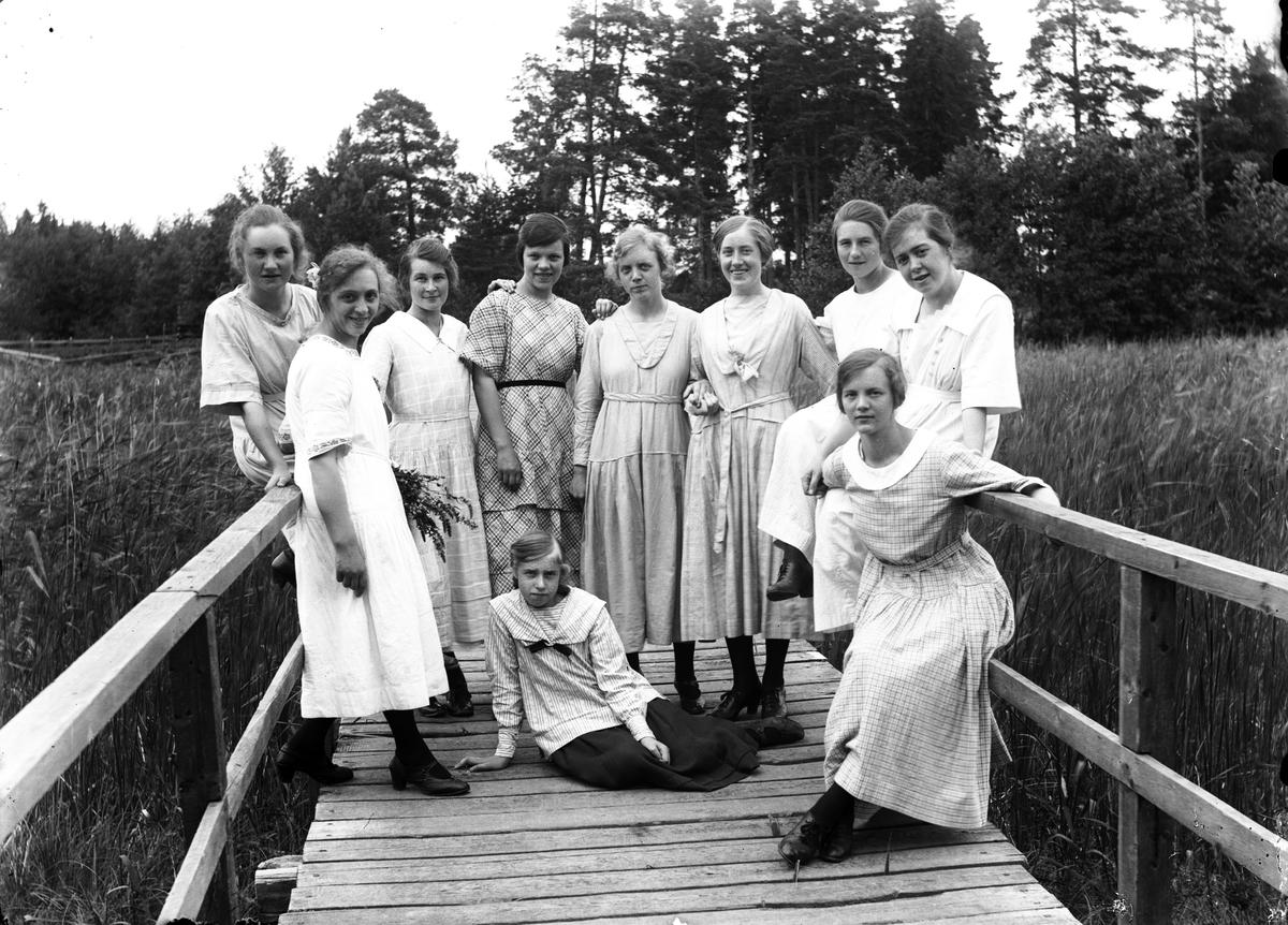 Tio flickor samlade på en träbro eller träbrygga.