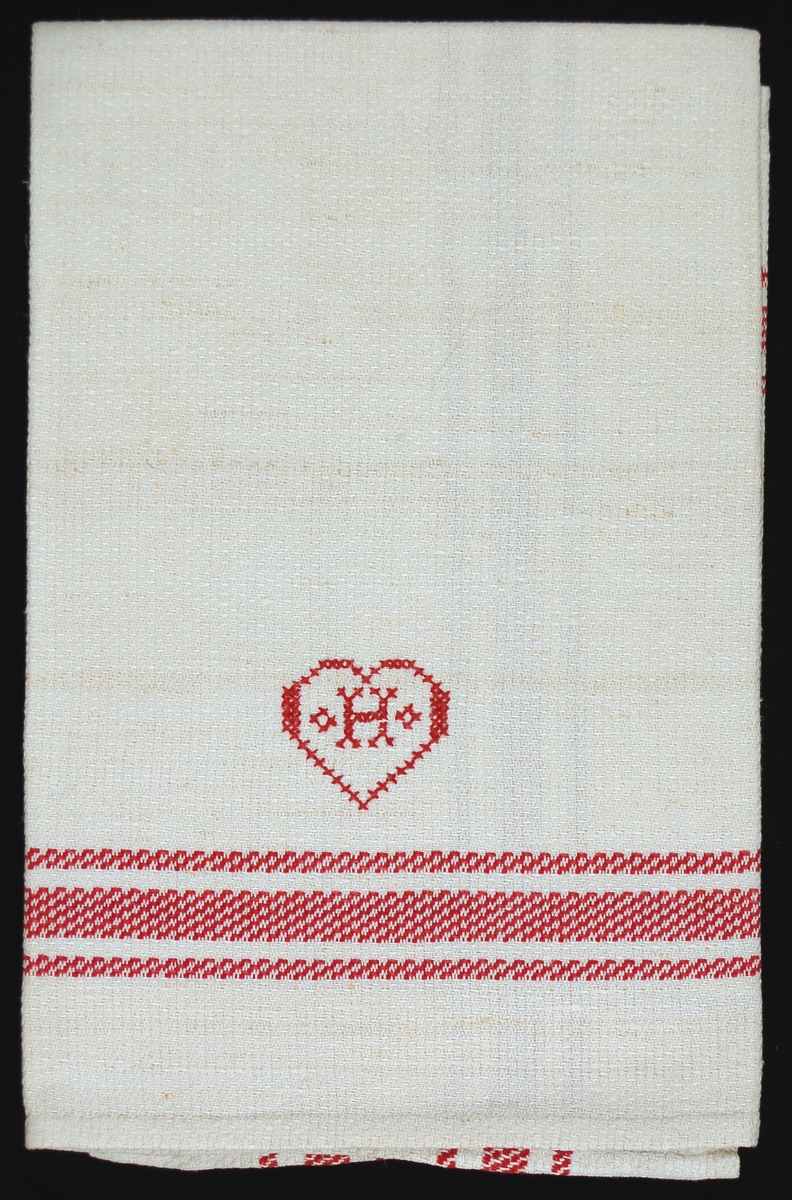 Handduk av hellinnedräll,oblekt linnevarpmmed röda inslag i rutor och ränder.Handfållad och försedd med en hank i oblekt bomull. I nedre delen av handduken finns broderat i korsstygn med rött bomullsgarn ett hjärta med ett H i mitten.