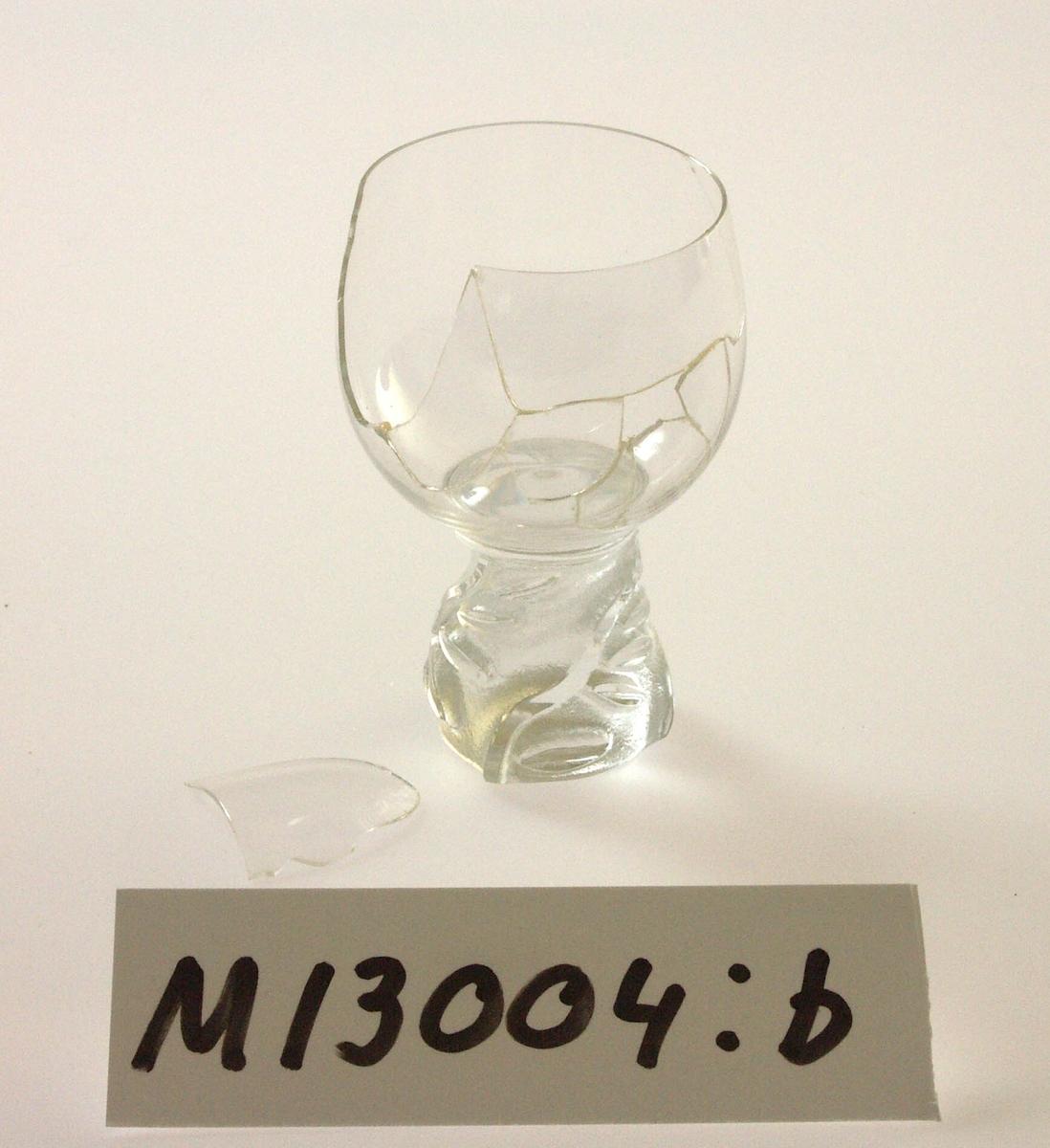 """Starkvinsglas tillhörande servis """"Skawonius 40"""".  Formgivet av Sven-Erik Skawonius. Konformig, tjock fot direkt på kuppan. Foten sandblästrad med utsparade, slipade partier i relief. Mönster av stilierade bladslingor. Ofärgat klarglas, foten delvis ogenomskinlig. Ovan angivna mått avser övre diameter. Fotdiameter: 37 mm. Inskrivet i huvudkatalogen 1943. Funktion: Starkvinsglas"""