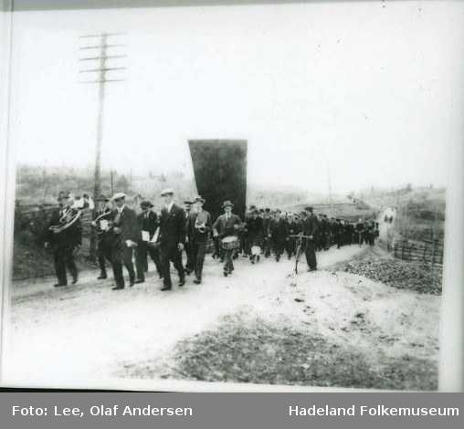 Musikkorps går foran en fane og et tog, 1. mai tog.